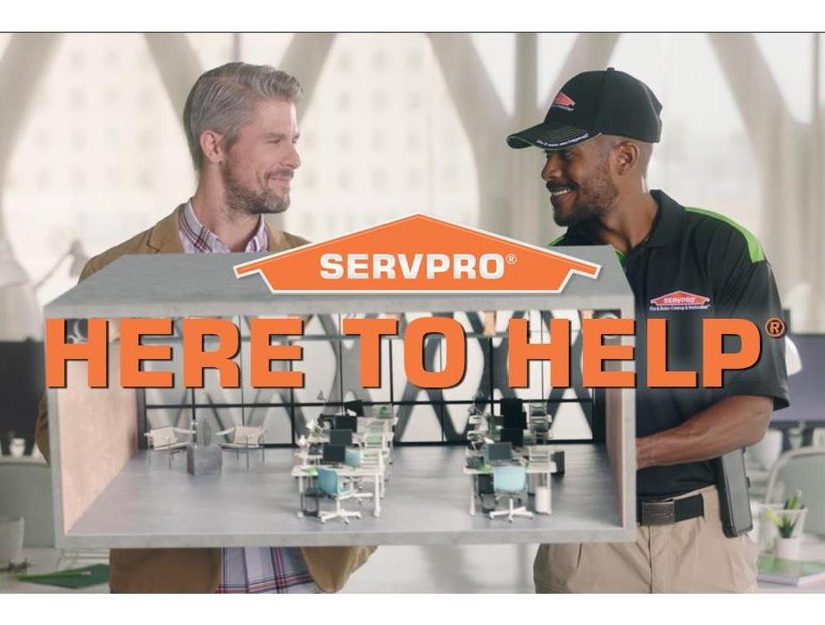 picture of 2 men with SERVPRO logo and the words saying here to help